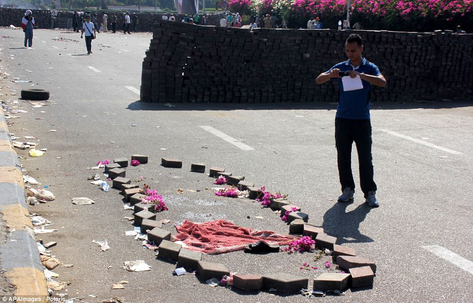 Flowers, a garment and bricks mark the spot where a Muslim Brotherhood supporter was killed by Egyptian security forces yesterday
