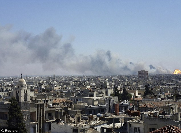 Panic: A giant plume of smoke trails above the city of Homs during the series of explosions one of which can be seen on the far right of the picture