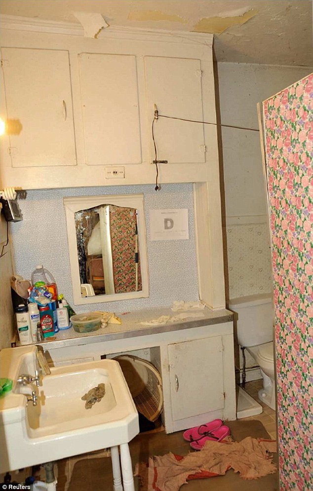 A view of a bathroom room in Ariel Castro's house featuring pink flowery wallpaper