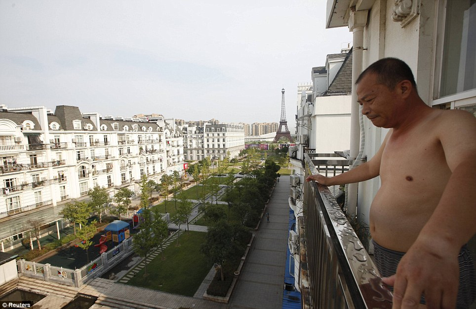Plush: This resident stands on the balcony of his apartment at the development, admiring the empty streets below