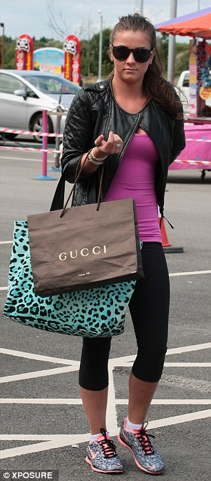 Brooke cut something of a different figure when she arrived carrying a Gucci bag over one arm before changing into her football gear (right)