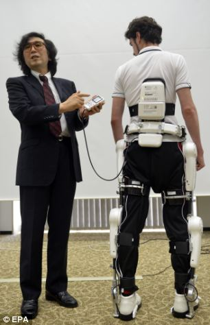 Cyberdyne's CEO Yoshiyuki Sankai, left, presents the medical 'Robot Suit HAL'