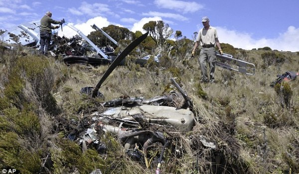 Members of a recovery team walk amongst the wreckage at the crash site of a light aircraft in the Aberdare National Park in Kenya