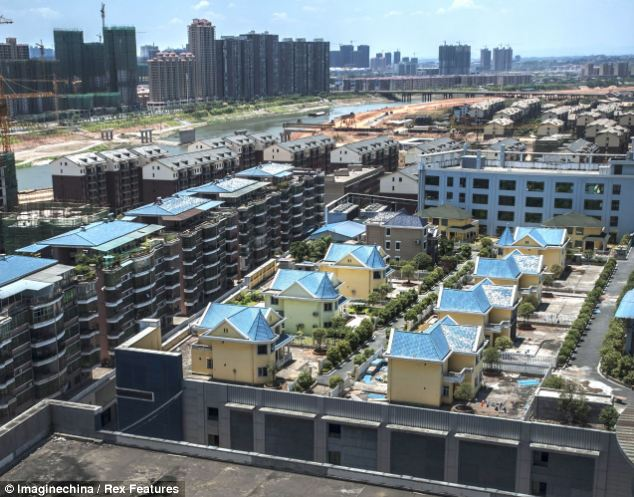 Pie in the sky: 25 luxury villas are now home to migrant workers after Chinese authorities said they were built illegally