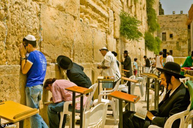 Jewish men pray at the wailing wall in Jerusalem