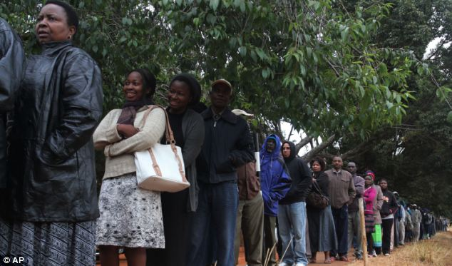 Democratic process: Voters who queued to take part in the elections were addressed by Mugabe, who said: 'We are delivering democracy on a platter'