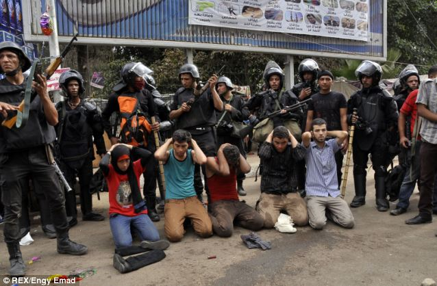 Arrested: Supporters of President Morsi are guarded by armed security forces after they were arrested following the clearing of two camps in Cairo this morning