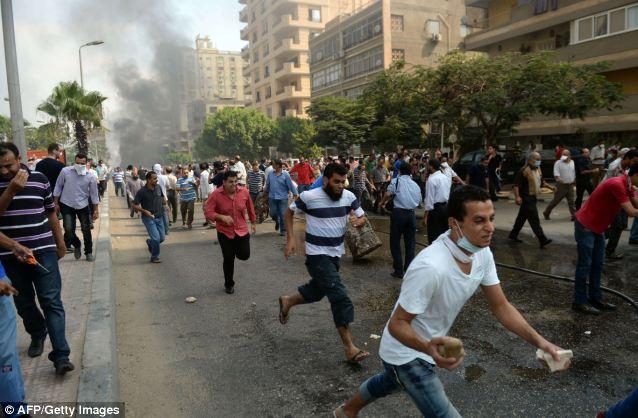 Fleeing: Egyptian Muslim Brotherhood supporters run from police in a street leading to Rabaa al-Adawiya protest camp