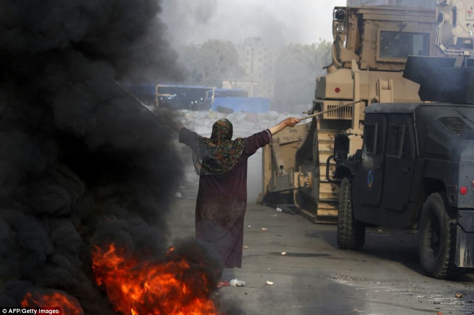 An Egyptian woman tries to stop a military bulldozer from going forward during clashes that broke out