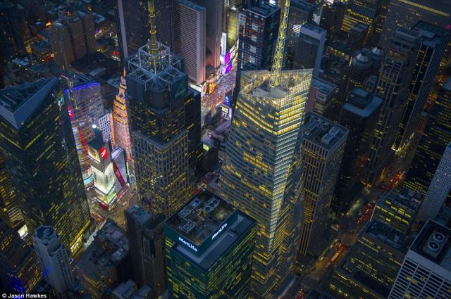 Midnight sun: In Midtown Manhattan, the vibrant, neon stretches of Times Square light up the night