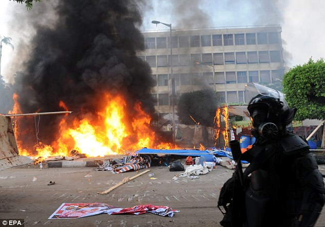 Bloodbath: Smoke rises as a tent burns at one of the two sites of the sit-in by the Egyptians supporting ousted president Mohamed Morsi at Nahda square near Cairo University on Wednesday