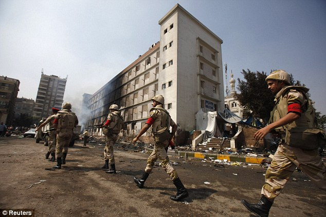 Response: Egyptian soldiers move near a burnt annex building of Rabaa Adawiya mosque after the clearing of a protest camp around the mosque
