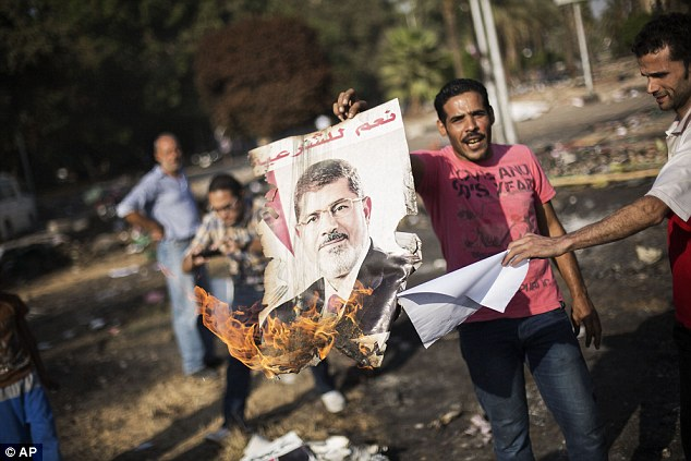 Flames: Egyptians against ousted President Morsi burn his poster amid charred debris of the Nahda sit-in camp