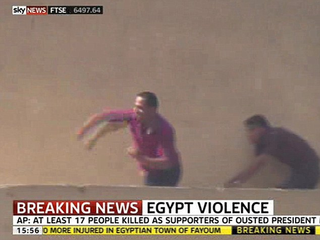 Violence: TV cameras captured these men on a rooftop throwing objects at the crowd below