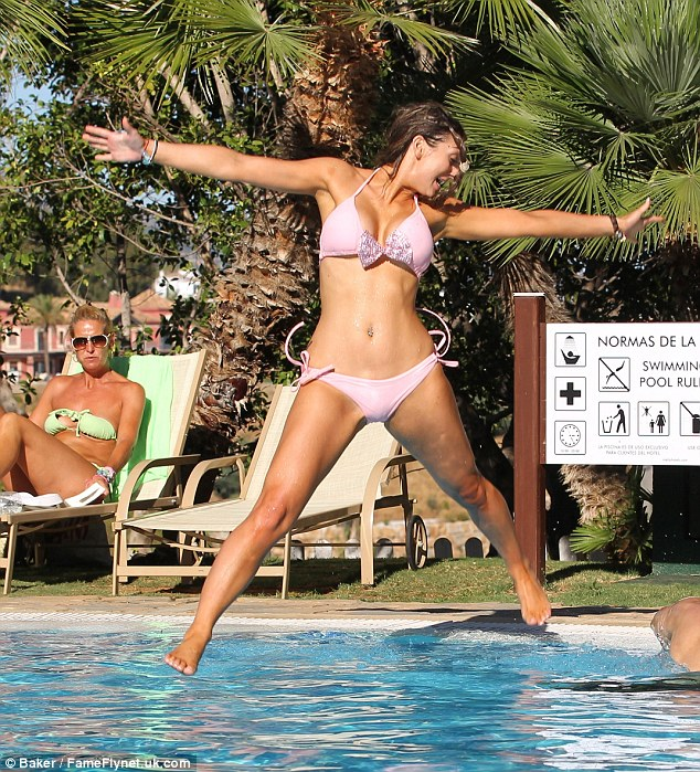 High energy: The businesswoman seemed in high spirits as she did a large star jump into the pool
