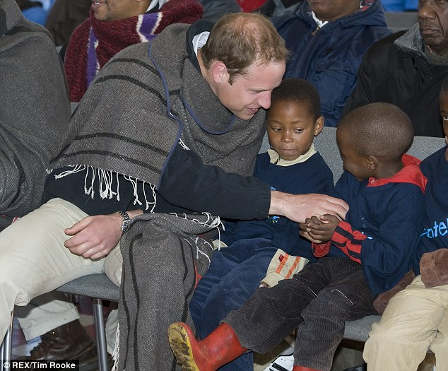 Having fun: Prince William tickles a young child in Lesotho, southern Africa, and the future king says he would like his son to experience the continent when he grows up