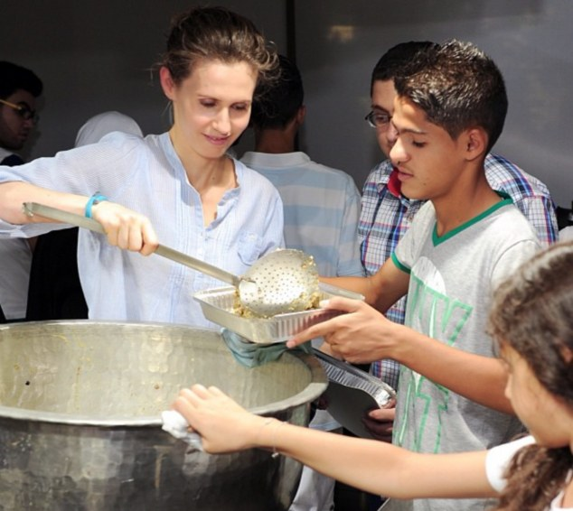 Backfire: Syrian first-lady Asma posted pictures of herself volunteering at a mobile kitchen, serving refugees which were not kindly received