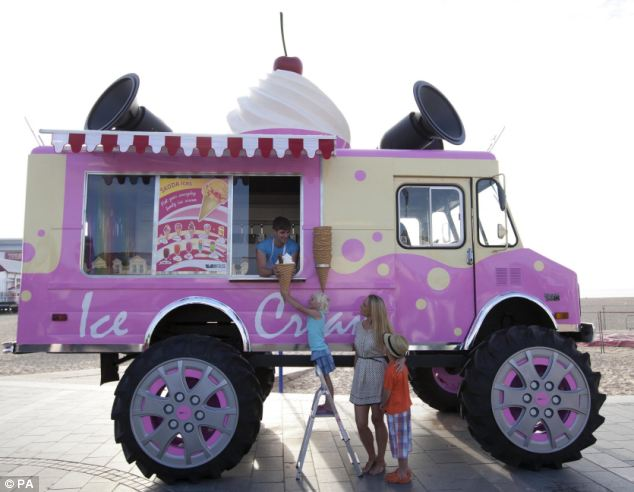 Five-year-old Charlotte has to stand on a stepladder to reach her over-sized ice cream from the giant van that is touring the country