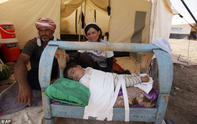 A Syrian family sits in a tent at Kawergost refugee camp in Iraq.