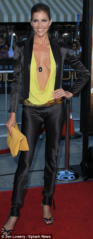 Dressed to impress: The actress donned black silk trousers with a matching blazer, which she teamed with a daring bright yellow cow neck top that fell almost to her navel, black stilettos and a mismatched yellow clutch