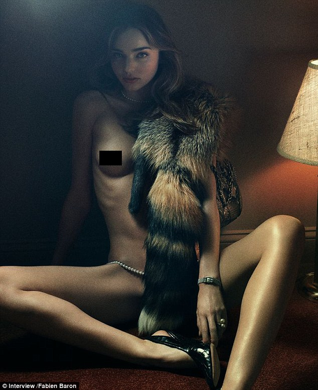 Raunchy: Miranda Kerr posed in nothing put a fur scarf, a designer handbag and some pearls for the racy shoot with Interview Magazine