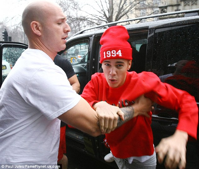 Scrapper: He had to held back by his own minders when he tried fight photographers in London in March.