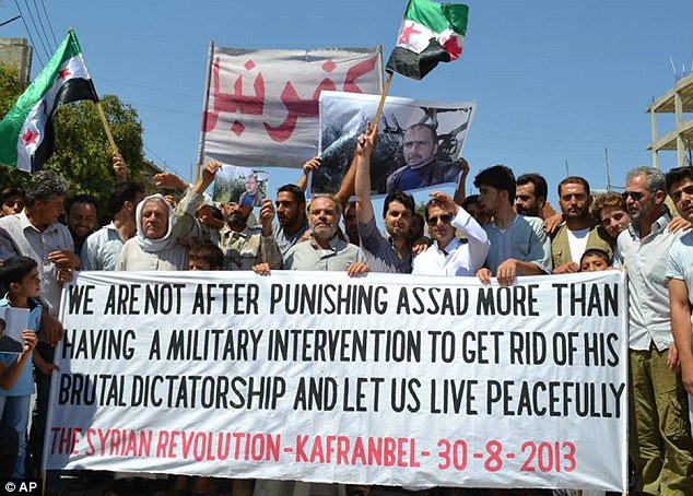 Protest: Anti-Syrian regime protesters carry a banner during a demonstration at Kafr Nabil in northern Syria