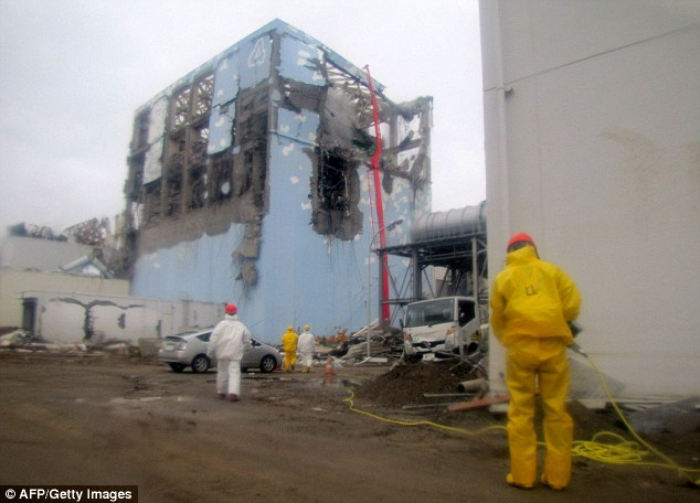 Dangerous: Workers spray water to cool down the spent nuclear fuel in the fourth reactor building at Fukushima in 2011