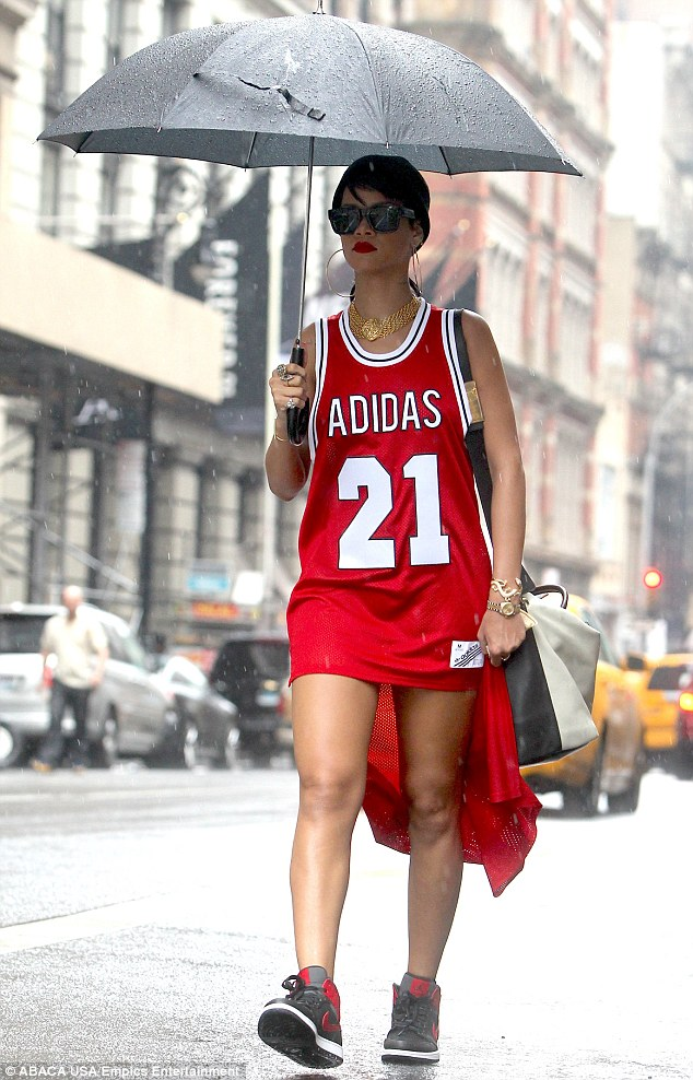 Under her umbrella: Rihanna bared her legs in an unusual basketball jersey dress as she braved the rain in New York on Monday