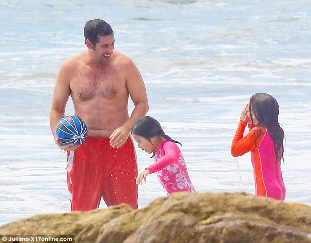 He was later seen laughing with his daughters Sunny, four, and Sadie, seven, both of whom looked adorable in their bright pink wetsuits