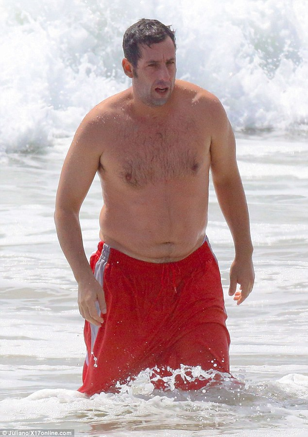 Extra weight: The Wedding Singer star displayed a noticeable paunch that hung over the waistband of his red board shorts