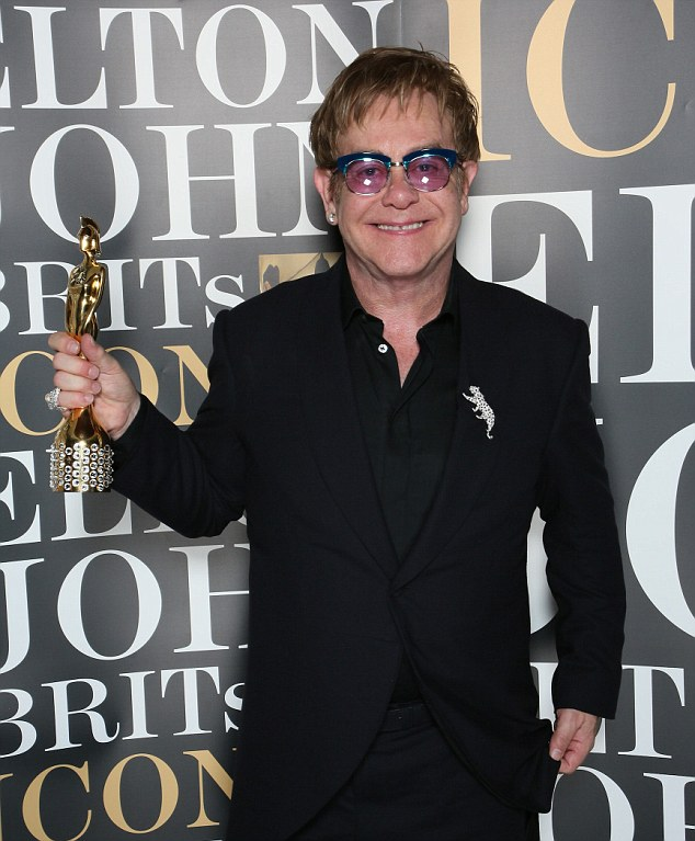 Legend: Elton John holds his Brits Icon Award which was presented to him at the London Palladium