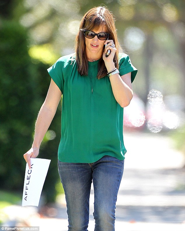 Big-name business: Before picking up her daughter, Jennifer was seen chatting on a phone as she held a piece of paper with her husband's last name written on it