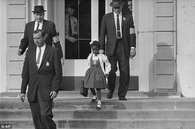 Heartbreaking: Ruby Bridges, 6, required three U.S. Marshals to escort her into Williant Frantz Elementary School in New Orleans, Louisiana, in 1960. U.S. Deputy Marshal Charles Burks, top left, never left her side