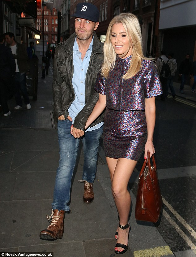 Cute couple: Offsetting her toned and tanned pins in the purple, blue and burgundy ensemble, the Saturdays star completed her look with a pair of black strappy skyscraper heels, while toting a stylish tan oversized handbag
