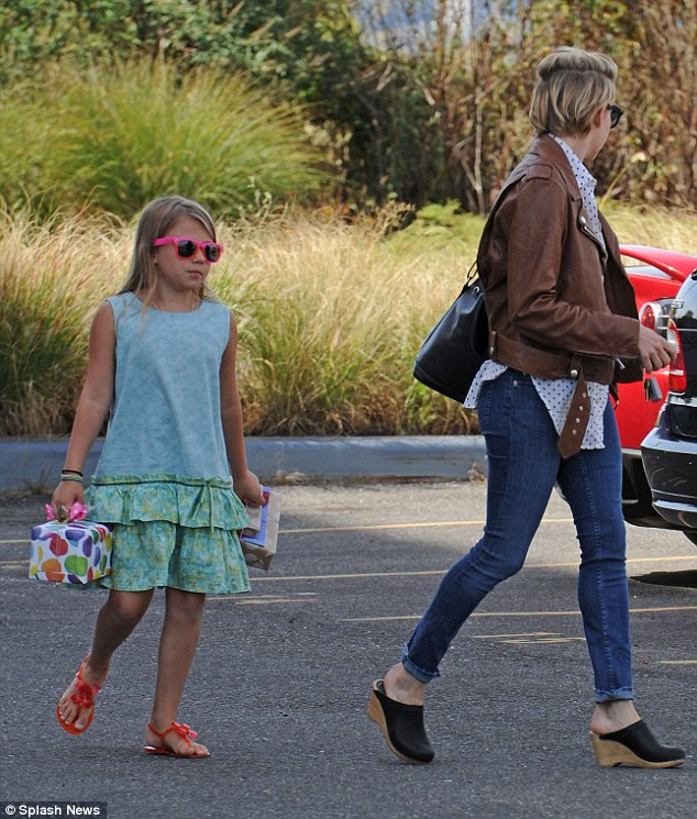 Mommy's little helper: The 7-year-old carries her mother's wrapped presents through a parking lot