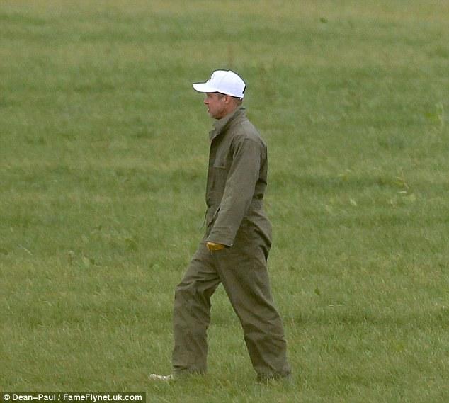 Walking in the wilderness: Brad was seen walking by himself across the grass fields - still wearing the baseball cap