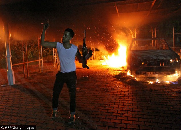 Under fire: An armed jihadist waves his rifle as buildings and cars are engulfed in flames after being set on fire inside the U.S. consulate compound in Benghazi late on September 11, 2012