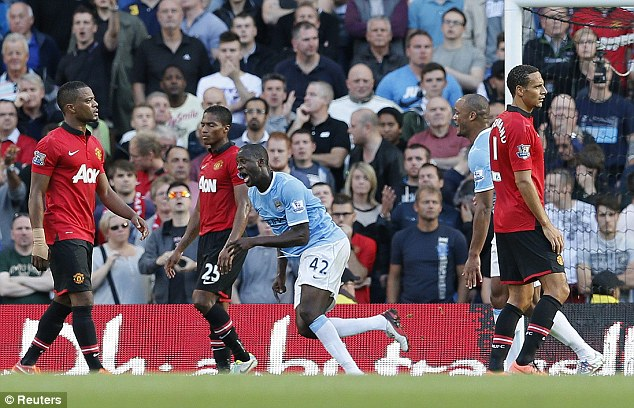 Derby delight: Yaya Toure celebrates putting City 2-0 up on the stroke of half time