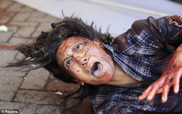 Désespoir: une femme blessée, dont le visage et les vêtements sont trempés dans le sang, se trouve sur le sol à l'extérieur du centre commercial crier à l'aide