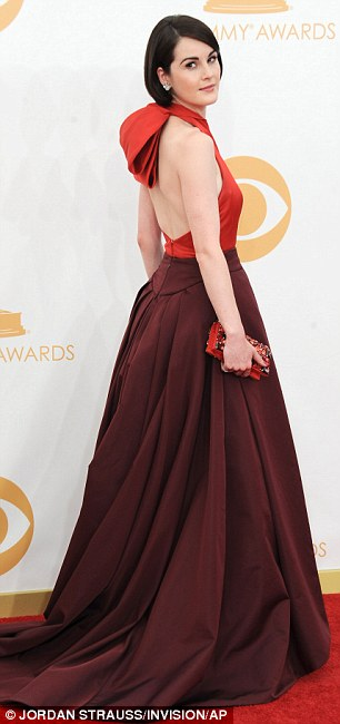 Oh dear! Downton Abbey star Michelle Dockery, 31, swamped her tiny frame in a voluminous orange and burgundy creation accented with a monstrous bow