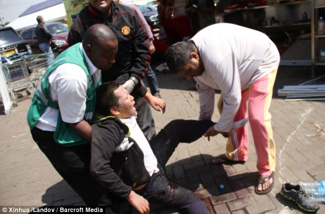 People help a wounded man outside the Westgate shopping mall, as 69 people were slaughtered by the terrorists