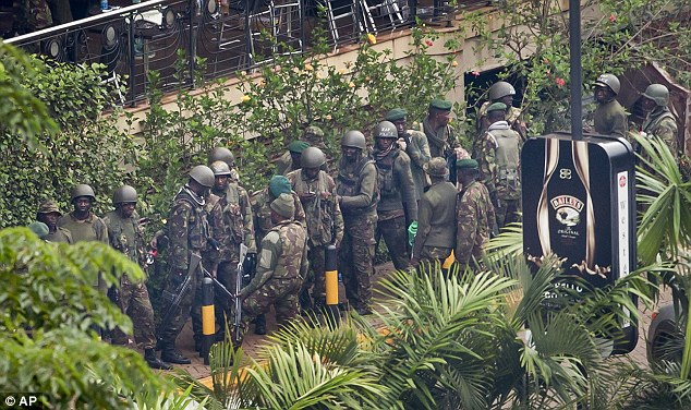 Ongoing operation: Kenyan soldiers gather at the entrance to the mall. Ten Britons are thought to have died in the massacre as it emerged the death toll could double to more than 130