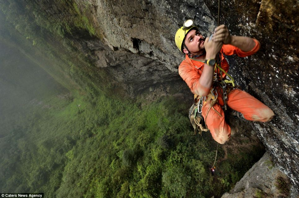 Explorer Duncan Collis (pictured) climbs a thin rope up to a small ledge