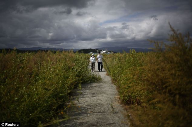 People wear face masks as they visit the cemetery at the tsunami destroyed coastal area of the evacuated town of Namie