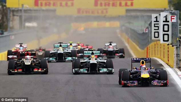 Ahead: Vettel makes a quick getaway from the start pursued by Hamilton and Grosjean