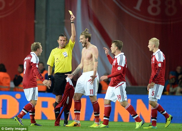 All smiles: Bendtner ignores the referee as he's shown a yellow card for removing his shirt after scoring