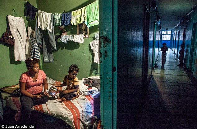Crowded: Laundry hangs over the bed in a tiny room shared by this family