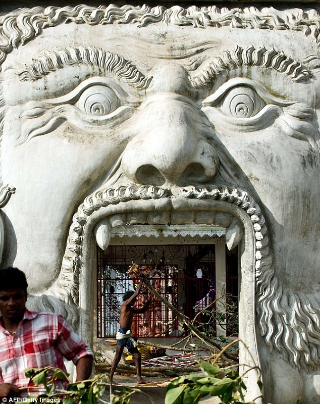 Open-mouthed: Local villagers remove fallen trees from a Goddess Kali temple at Gopalpur Junction in India