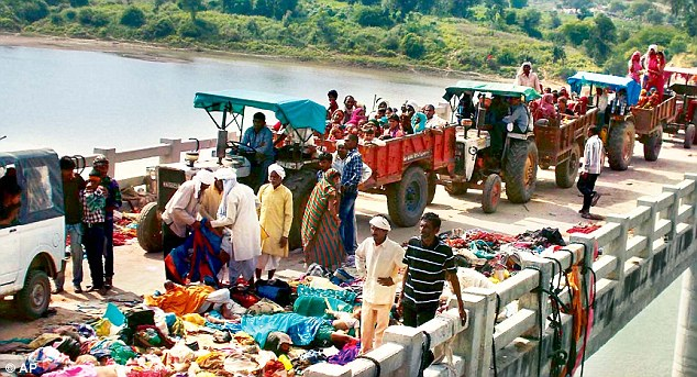 Indian villagers on tractors move past bodies of victims of a stampede on a bridge across the Sindh River in Datia district in Madhya Pradesh state, India